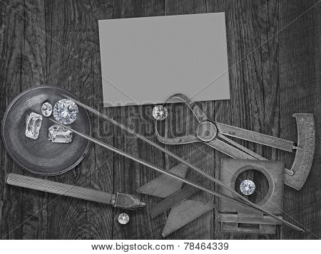 black and white image of a vintage jeweler tools and diamonds over wooden bench, blank card for your business