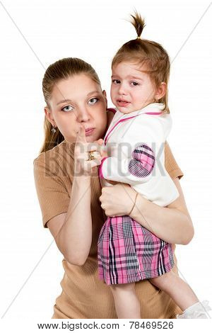 Little daughter crying on his mother arms which indicates forefinger at the camera isolated on a white background poster