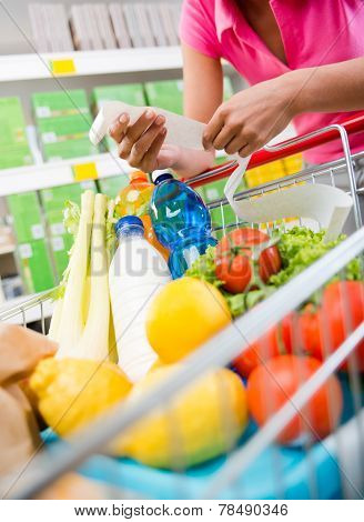 Unrecognizable woman checking a long grocery receipt leaning to a full shopping cart at store. poster