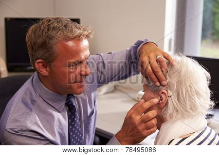 Doctor Fitting Senior Female Patient With Hearing Aid