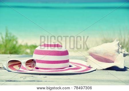 Sun glasses and hat against tropical beach of Great Exuma island, Bahamas