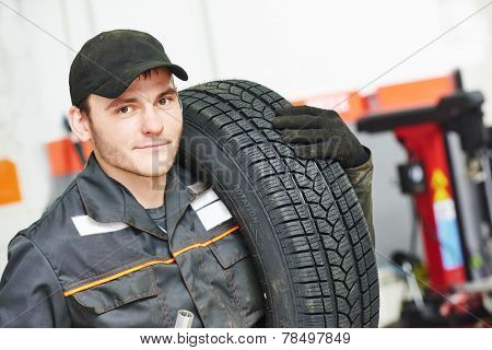 repairman mechanic portrait in car auto repair or maintenance shop service station with automobile wheel tire poster