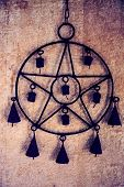 Pentagram wind chime with bells hanging against yellow stucco wall poster
