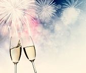 Toasting with two champagne glasses against fireworks and holiday lights poster