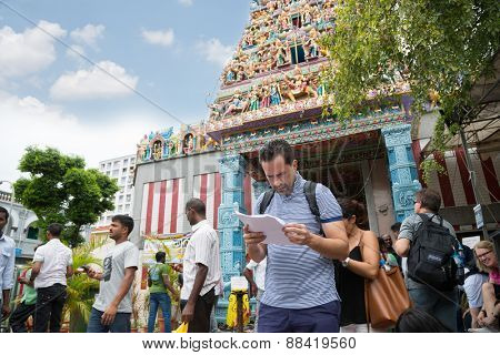 SINGAPORE - FEBRUARY 19, 2015: European tourist on background indian Hinduism temple in Little India. Little India or the Indian quarter, a very popular area with tourists visiting Singapore.