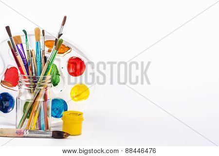 isolated paints brushes in a glass and yellow water paint
