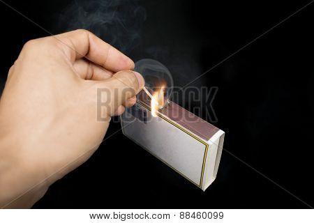 Striking a match against a match box. poster