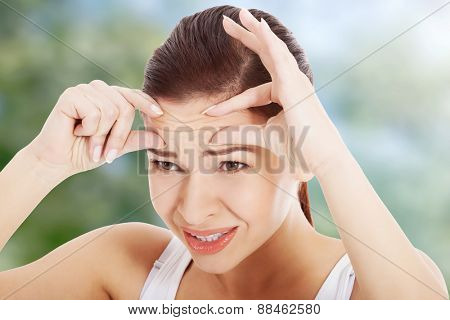 Shocked woman checking wrinkles on forehead.