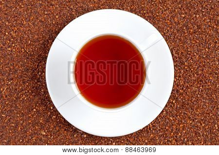 Healthy South Africa traditional beverage tea rooibos in white cup on rooibos tea background texture. Top view. poster