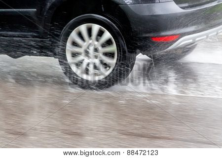 car driving in the rain on a wet road. danger of aqua planning and accidents poster