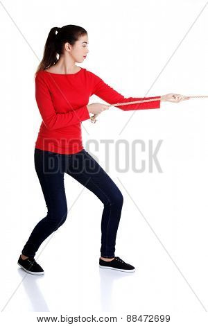 Full length strong woman puling rope.