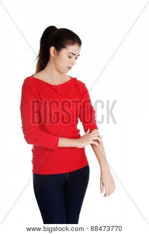 Young beautiful woman scraching herself.