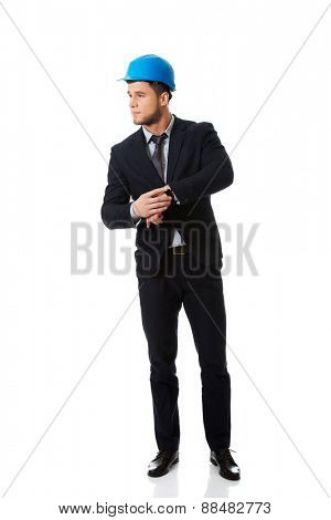 Businessman in hard hat checking time on his wrist watch.