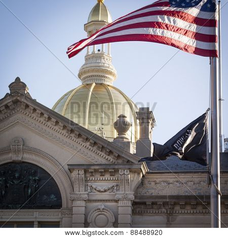 TRENTON, NJ - APRIL 4, 2015: The American Flag waves in front of the gold dome rotunda of the New Jersey State House located in Trenton. The capitol building for the state NJ is located on State St.