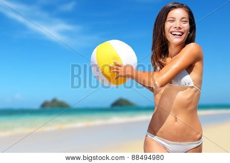 Beach fun summer vacation woman playing with ball in water. Beautiful white sand Hawaiian beach background with the iconic Lanikai Mokulua islands on Oahu, Hawaii, USA. Asian playful in ocean waves.