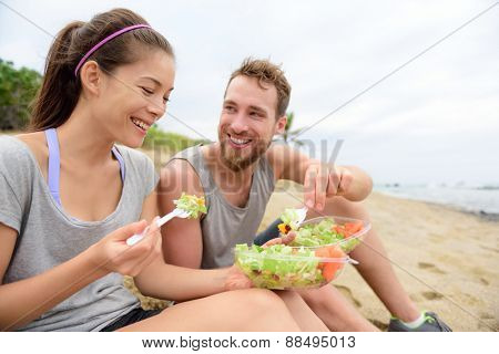 Happy young people eating healthy salad for lunch. Multiracial group having a break on beach snacking on a vegan takeaway meal of green veggies and carrots laughing together. Casual lifestyle. poster
