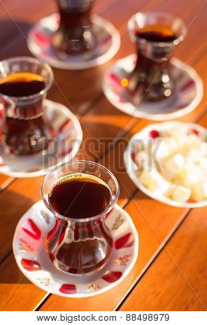 Turkish tea with teapot and locum in outdoor cafe. Direct sunset light. Shallow DOF and lightly toned poster