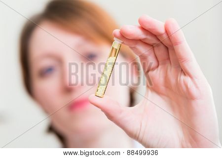 Alternative practitioner holding homeopathy globuli in tube