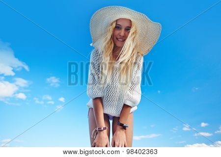 Happy girl in pullover and sunhat looking at camera against blue sky poster