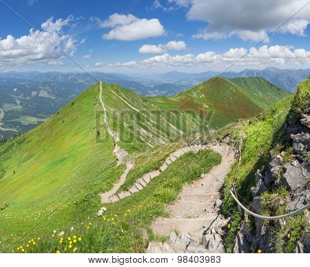 Ridge trail in the green summery Alps