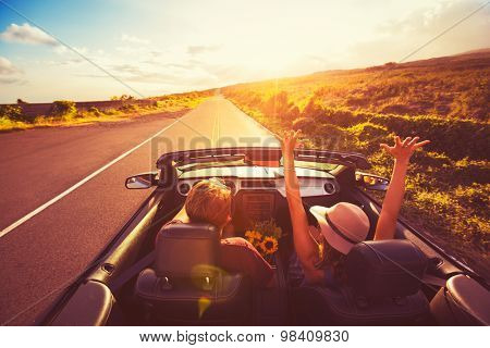 Happy Young Couple Driving Along Country Road in Convertible at Sunset. Freedom Adventure Road Trip
