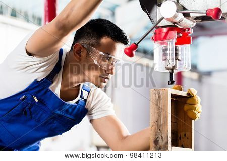 Asian worker on drilling machine in production factory or manufacturing plant