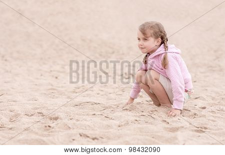 little girl kneeling on the sand and looking ahead