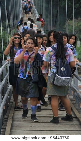 schoolgirls are walking on the bridge in small village Bukit Lawang