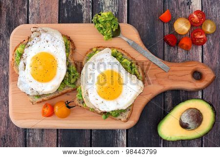 Avocado, egg open sandwiches on paddle board