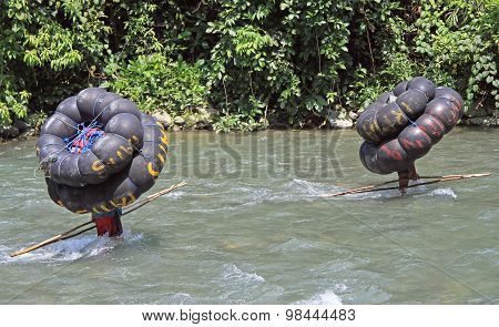 two men are carrying tube, Bukit Lawang