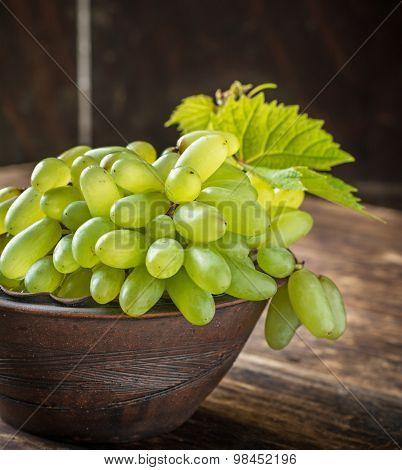 Grape varieties of ladies' fingers in a brown pottery bowl handmade
