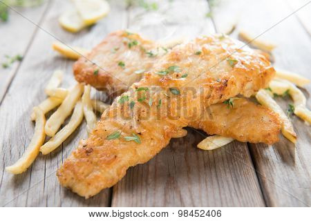 Fish and chips. Fried fish fillet with french fries on old wooden background. Fresh cooked with hot steams.