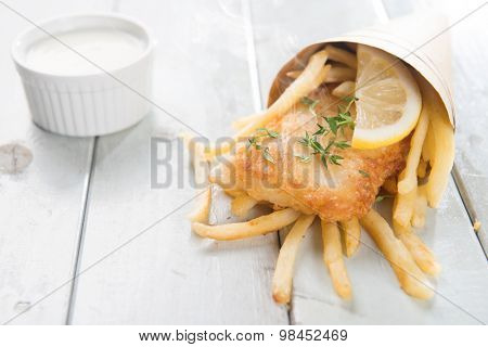 Fish and chips. Fried fish fillet with french fries wrapped by paper cone, on wooden background. Fresh cooked with hot smoke.