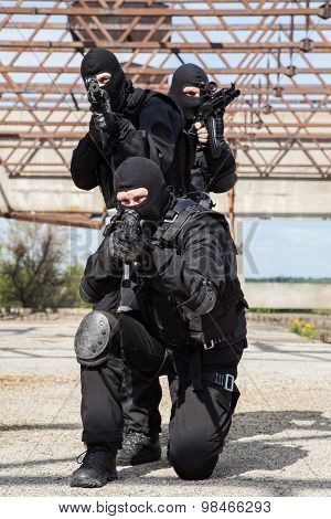 Special forces operators in black uniform in action poster