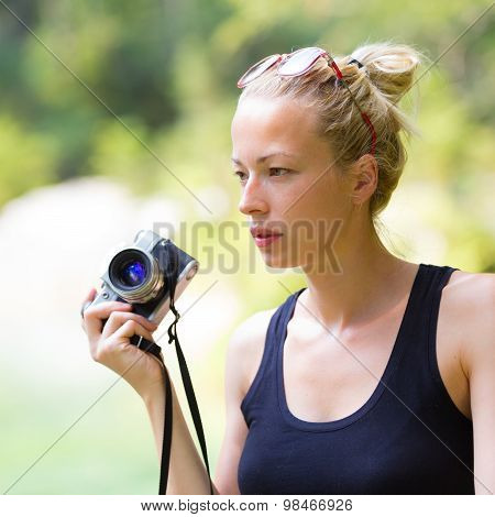 Woman in nature with retro camera.