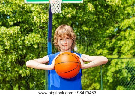 Boy holds ball alone during basketball game