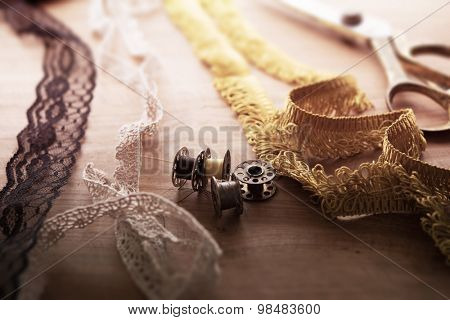 Fringe or lace tapes and silk trimmings with gold (brass) scissors and old sewing machine bobbins on a old grungy work table. Tailor's work table. textile or fine cloth making.Shallow depth of field.