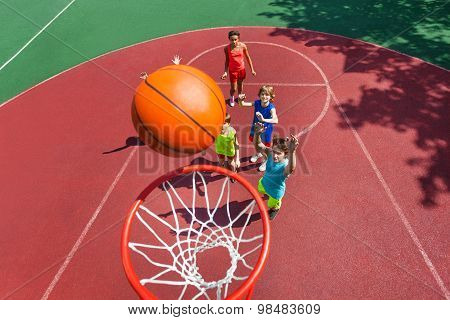 View of flying ball to basket from top, teens play