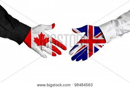 Canadian and British leaders shaking hands on a deal agreement