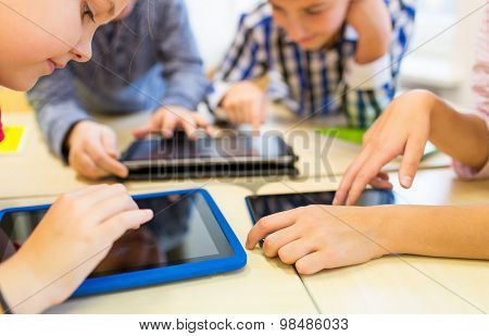 education, elementary school, learning, technology and people concept - close up of school kids with tablet pc computers having fun and playing on break in classroom