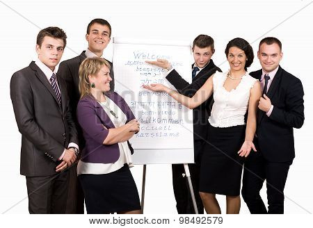 Team of five business consultants welcomes participants of conference. Five business looking people stay next to flip chart with WELCOME sign written in many languages poster