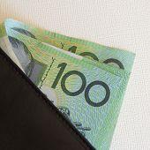 A wallet full of Australian hundred dollar notes. poster