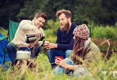 adventure, travel, tourism and people concept - group of smiling friends cooking food in dixie sitting around bonfire outdoors poster