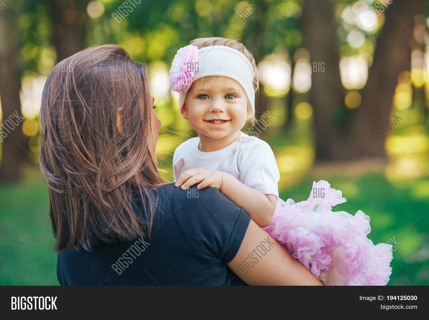 A Beautiful Brunette Mom Is Holding His Little Daughter In The Park