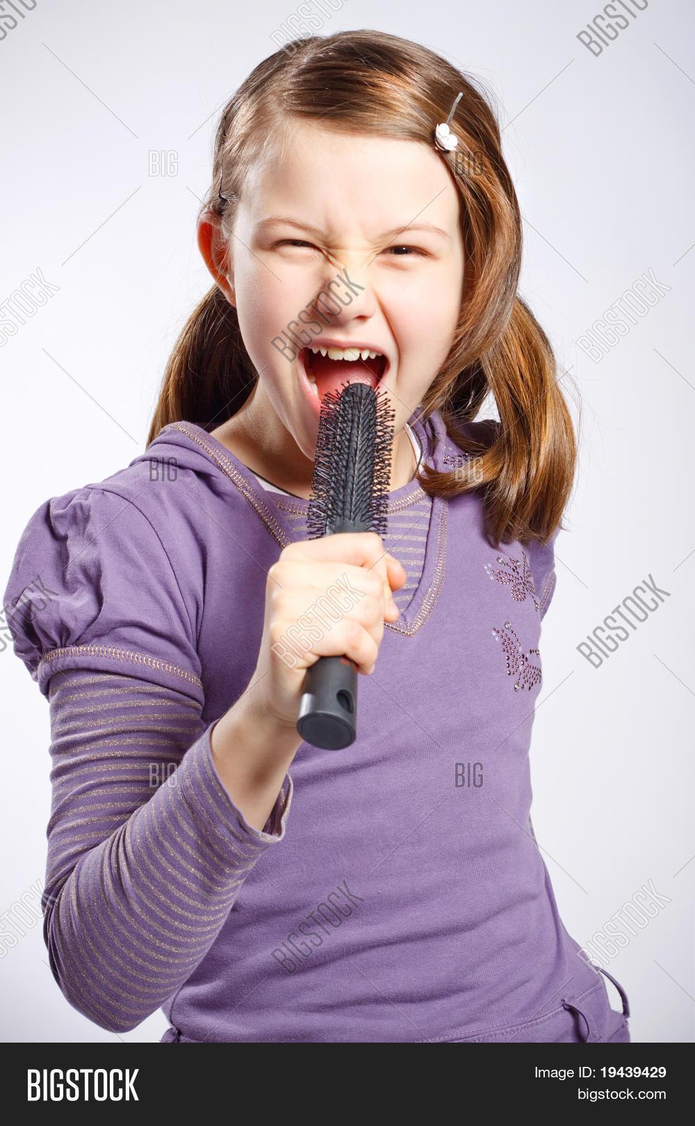 niña cantando usando un cepillo para el pelo como micrófono d64948123c15