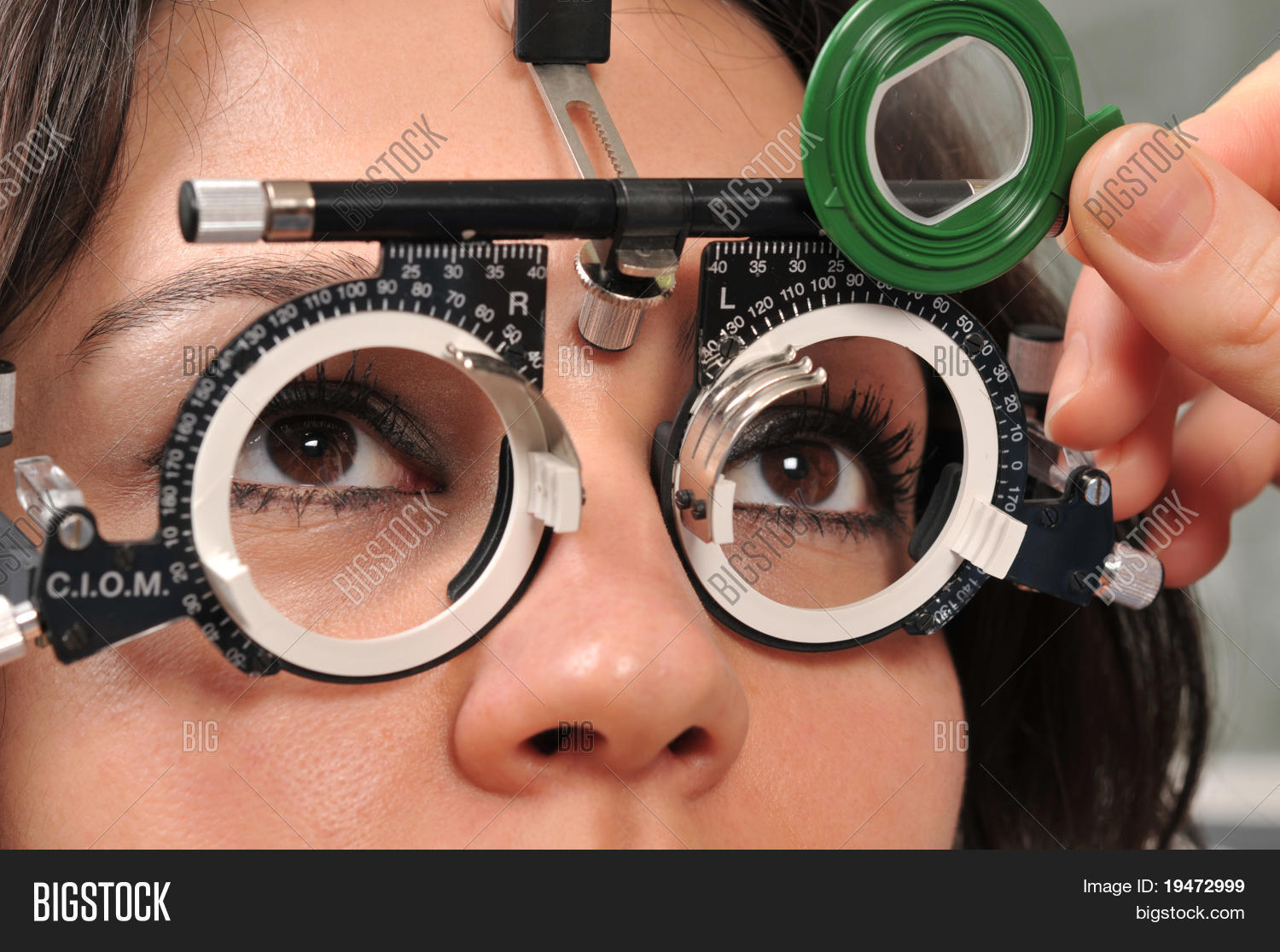 a99f0f1981c Beautiful young female patient having a medical examination at optician - a  series of eye exam