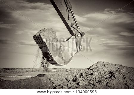 Excavator arm and scoop full of dirt at construction site against sky, black and white, sepia toned image