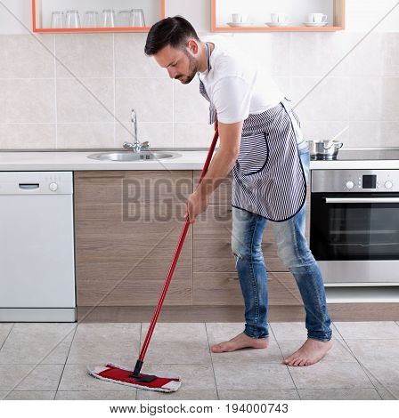 Man Mopping Floor In Kitchen