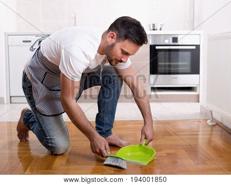 Man Sweeping Dust On Parquet