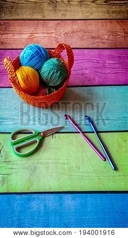 Colorful balls of yarn in wicker basket on old multicolored background